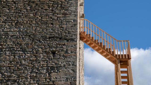 Eine Holztreppe an der Fassade eines Steinturms.
