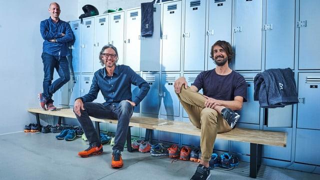 Drei Männer sitzen in einer Garderobe