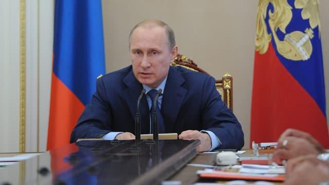 Wladimir Putin sitzt in einem beflaggten Raum