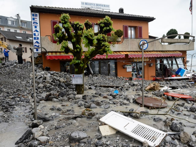 Vor einem Resturant wurden Tische, Fensterläden und andere Gegenstände angeschwemmt.