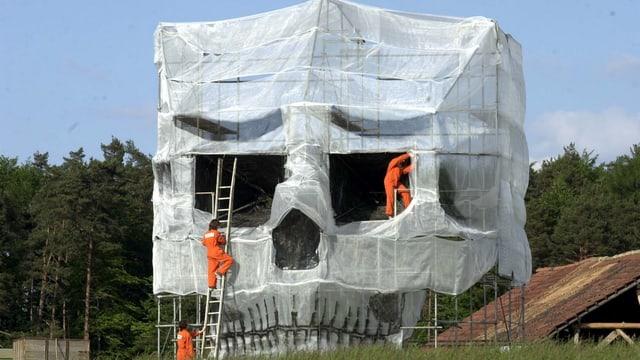 Greenpeace-Deponiebesetzer enthüllen ein monumentales Mahnmal in Form eines Totenkopfes.