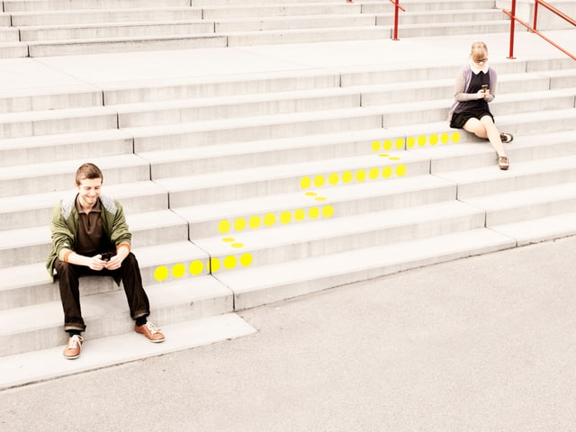 Ein Mann sitzt auf einer Treppe. Er schaut lächelnd in ein Smartphone. Eine gepunktete Linie führt von ihm weg die Treppe hinauf.