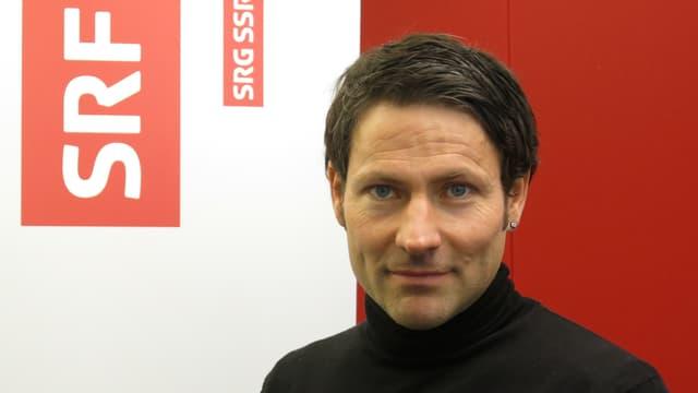 Eric Rütsche posiert vor einem SRF-Logo und schaut in die Kamera.