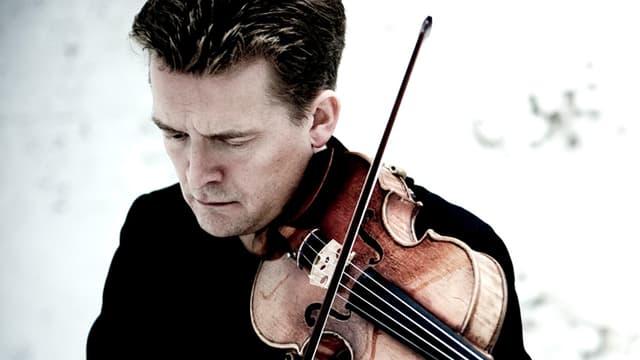 Ein Mann in scharzem Anzug spielt mit geschlossenen Augen Geige.
