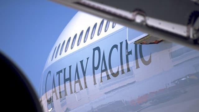 Schriftzug Cathay Pacific an einem Flugzeug von unten fotografiert mit einem Teil des Flügels im Vordergrund