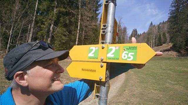 SRF 1 Wanderexperte Marcel Hähni vor einem Wanderwegweiser.