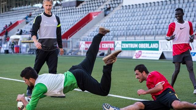 Flüchtlinge kämpfen im Training im Thuner Stadion um den Ball.