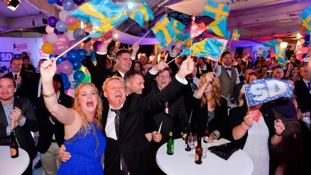 Jubelnde Parteimitglieder schwenken Schweden-Flaggen.