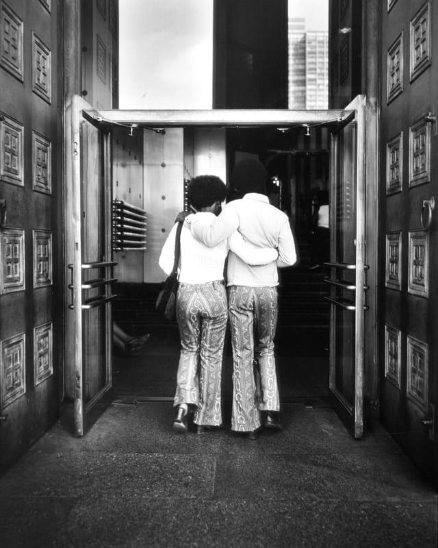 Ein Paar im Partnerlook geht durch eine offene Flügeltür.