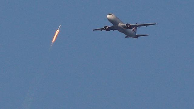 Rakete fliegt in den Himmel, Flugzeug daneben.