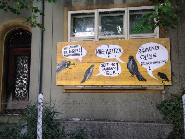 Ein verbarrikadiertes Fenster mit aufgeklebten Vogel und Sprechblasen. Die Vögel protestieren dagegen das Haus leer stehen zu lassen.