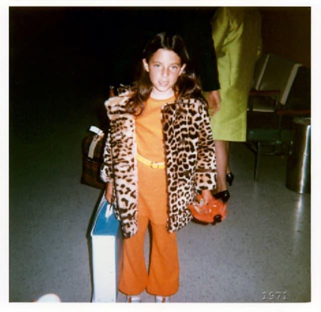 Ein kleines Mädchen im orangefarbenen Overall mit Leopardenmantel schaut in die Kamera.