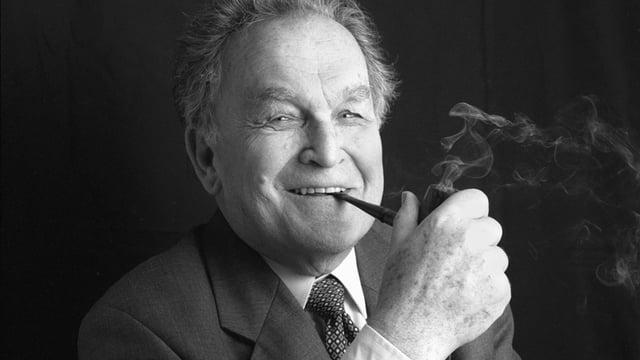 Schwarz-weiss-Aufnahme von Otto Stich, er raucht Pfeiffe, hält mit der rechten Hand die Pfeiffe, aus der ein wenig Rauch aufsteigt. Er trägt einen Anzug mit Krawatte, und lächelt in die Kamera.