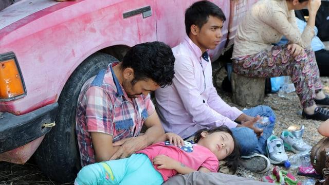 Menschen lehnen erschöpft an ein pinkes Auto an, ein Mädchen schläft auf eines Mannes Schoss.