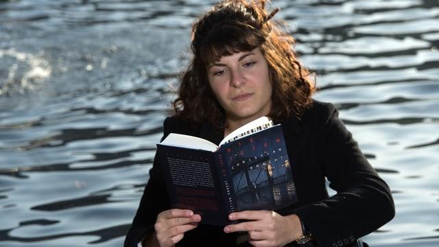 Eine junge Frau liest ein Buch vor einem Brunnen.