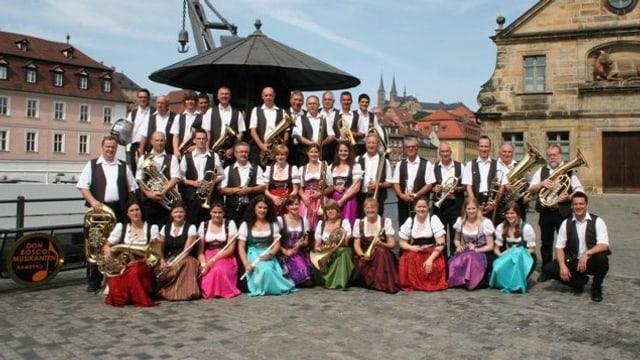 Eine Blasmusikformation mit Musikanten und Musikantinnen in bunten Kleidern.