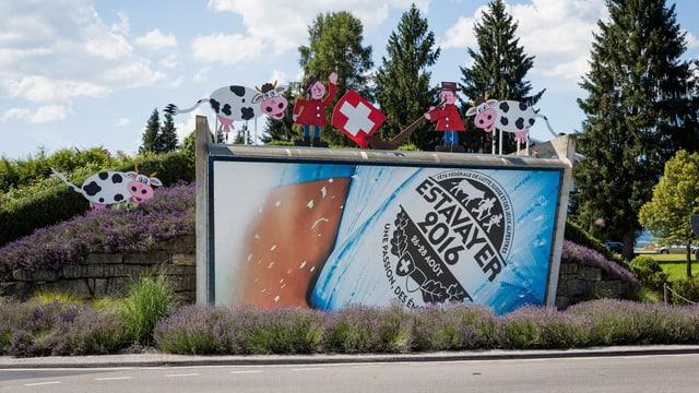Das Festlogo an einer mit Blumen, Kühen, Fahnenschwinger und Alphornbläser geschmückten Mauer.