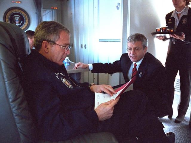 George W. Bush sitzt in einem Sessel an Bord der «Air Force One» und liest ein Papier – neben ihm hockt ein Mitarbeiter.
