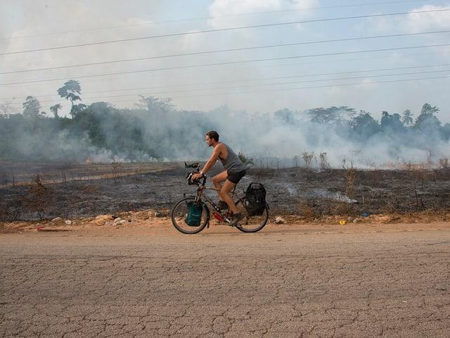 Lukas Biry fährt auf einer Strasse, im Hintergrund brennen und qualmen Büsche.