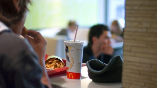 Ein junger Mann beisst in einem Mc-Donalds-Restaurant in einen Burger. In Hintergrund sind weitere Gäste.