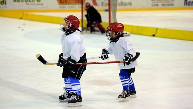 Zwei Kinder in Eishockey-Montur auf dem Eisfeld