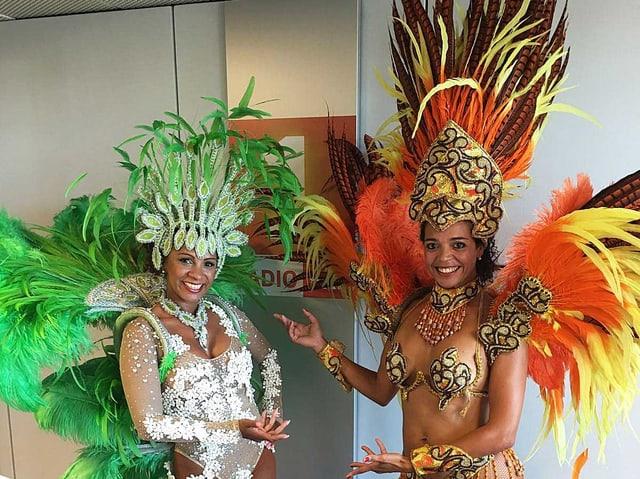 Zwei Frauen im Federschmuck-Kostüm.
