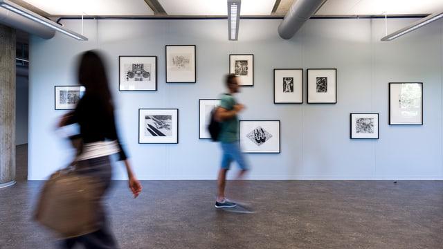 Schüler gehen vor einer Wand mit mehreren Bildern.
