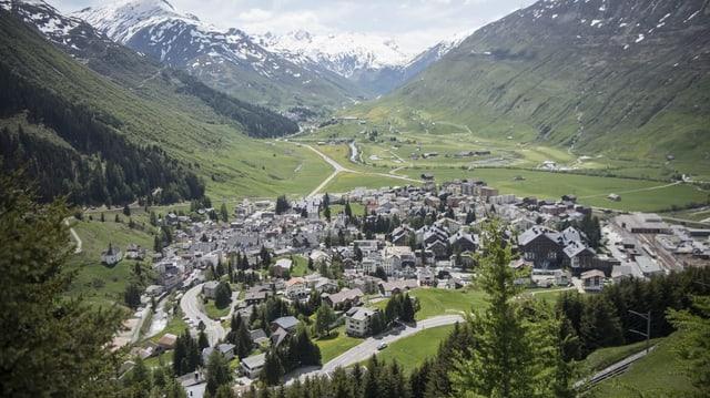 Blick auf das Dorf Andermatt mit Schneebergern im Hintergrund.