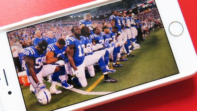 Spieler der Indianapolis Colts knien, während die Hymne spielt. Sie machen das aus Protest.
