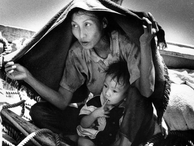 Eine Frau hat ein kleines Kind auf dem Schoss. Sie schützt sich und ihr Kind mit einem Stück Tuch vor der Hitze. Sie befinden sich auf einem Boot.