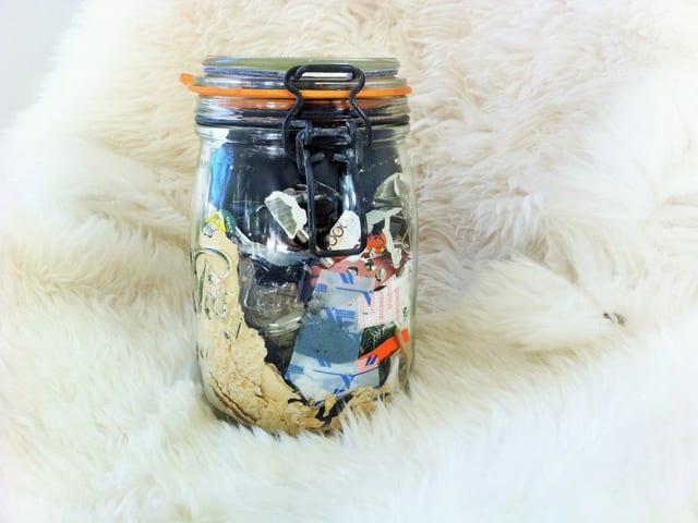 Ein Einmachglas mit Abfall steht auf einem Schafsfell.
