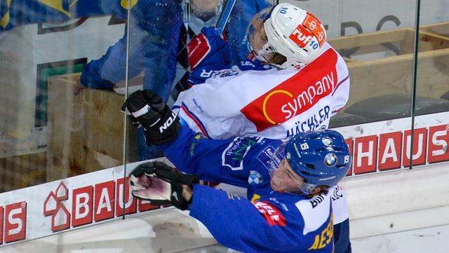 Ein Hockey-Spieler in blauem Dress drückt seinen Gegenspieler mit voller Wuche an die Bande aus Glas.