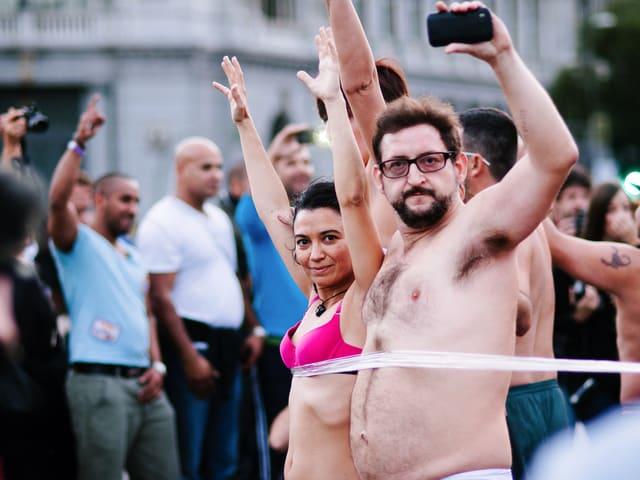 Demonstranten ziehen während einer Demonstration ihre Kleider aus.