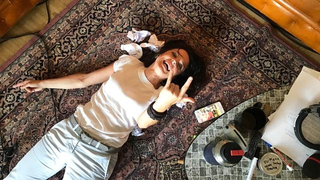 Mona Vetsch auf dem Boden, macht Metal-Handzeichen.