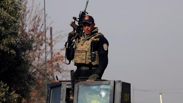 Ein Soldat einer irakischen Spezialeinheit mit Gewehr auf einem Fahrzeug.