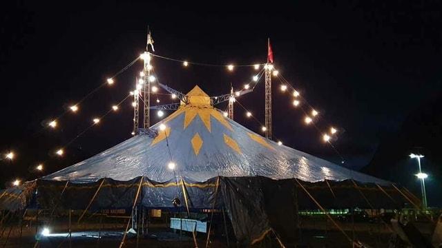 Das hell erleuchtete Zirkuszelt bei Nacht.