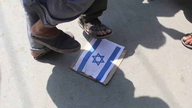 Füsse treten auf ein Bild der israelischen Flagge, das auf dem Boden liegt.