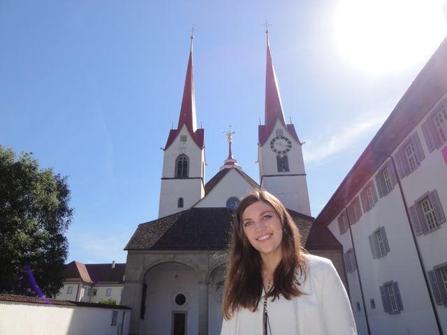 Eine Frau steht vor einer Kirche