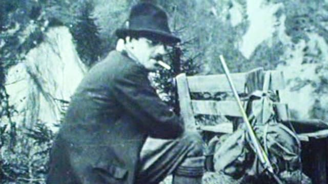 Meinrad Inglin im Hochgebirge mit Hut, Zigarre rauchend, Gewehr an Bank gelehnt