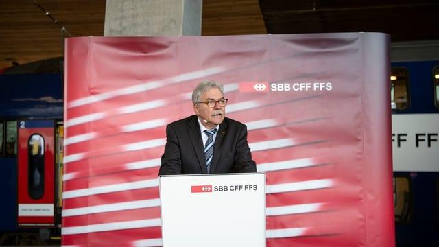 Toni Häne, grau meliert und in schwarzem Anzug, an einem Rednerpult, dahinter eine Stellwand der SBB.