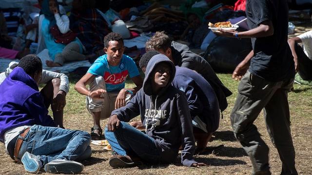 Flüchtlinge in einem Park sitzend.