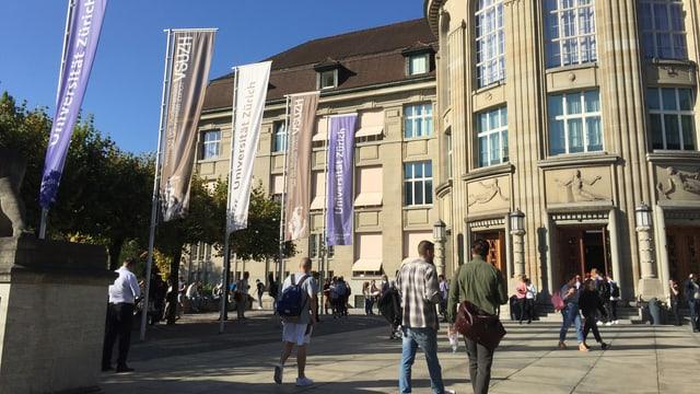 Blick auf den Haupteingang der Uni Zürich, links Flaggen, im Vordergrund Studierende.