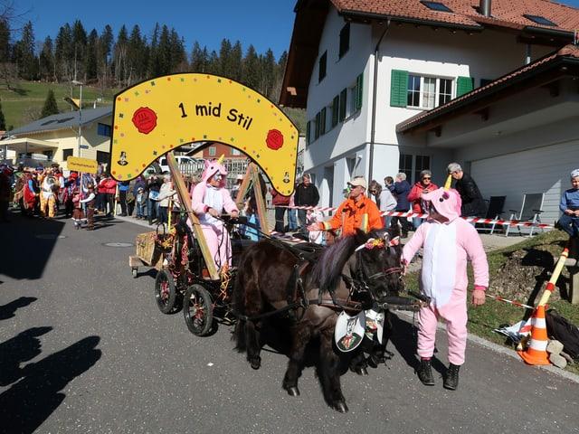 Zwei Ponys, welche eine Kutsche ziehen, auf der jemand mit einem Schild drauf ist.