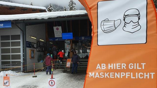 Ein Schild weis vor einem Skilift auf die geltende Maskenpflicht hin.