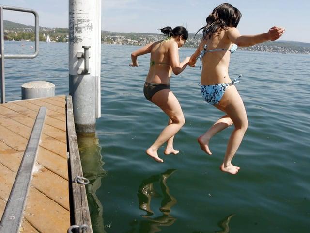 Mädchen springen vom Steeg in den See.