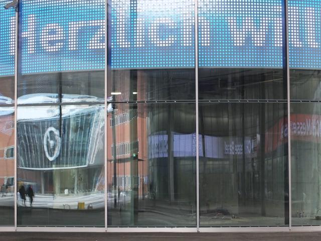 Glastüren des Eingangs, darin spiegelt sich der Rundhofbau.