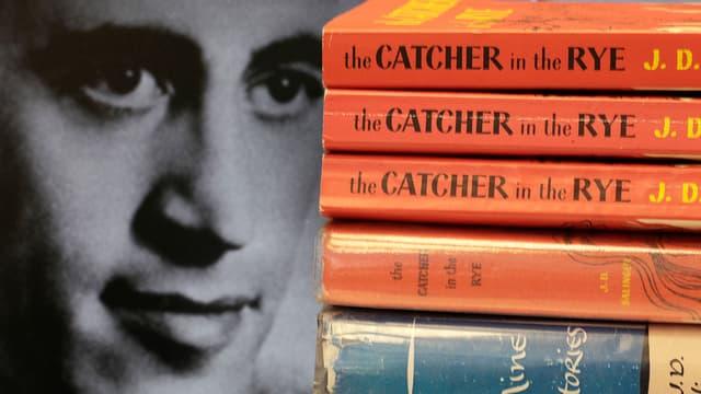 Schwarzweisse Porträtaufnahme, am rechten Bildrand ein Stapel «The Catcher in the Rye»-Bücher.