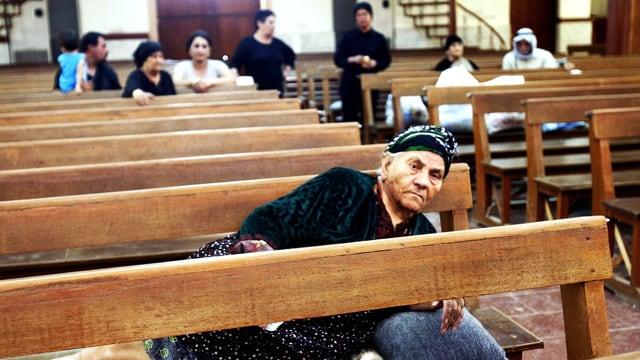 Eine Frau liegt auf einer Kirchenbank
