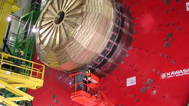Messingscheiben montiert auf einem riesigen Detektor. Im Vordergund, klein, zwei Techniker.
