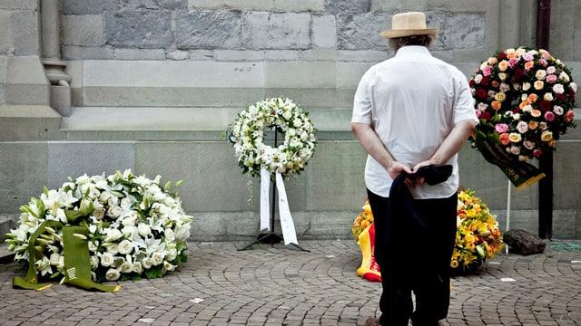Ein Mann betrachtet Blumenkränze an einer Trauerfeier.